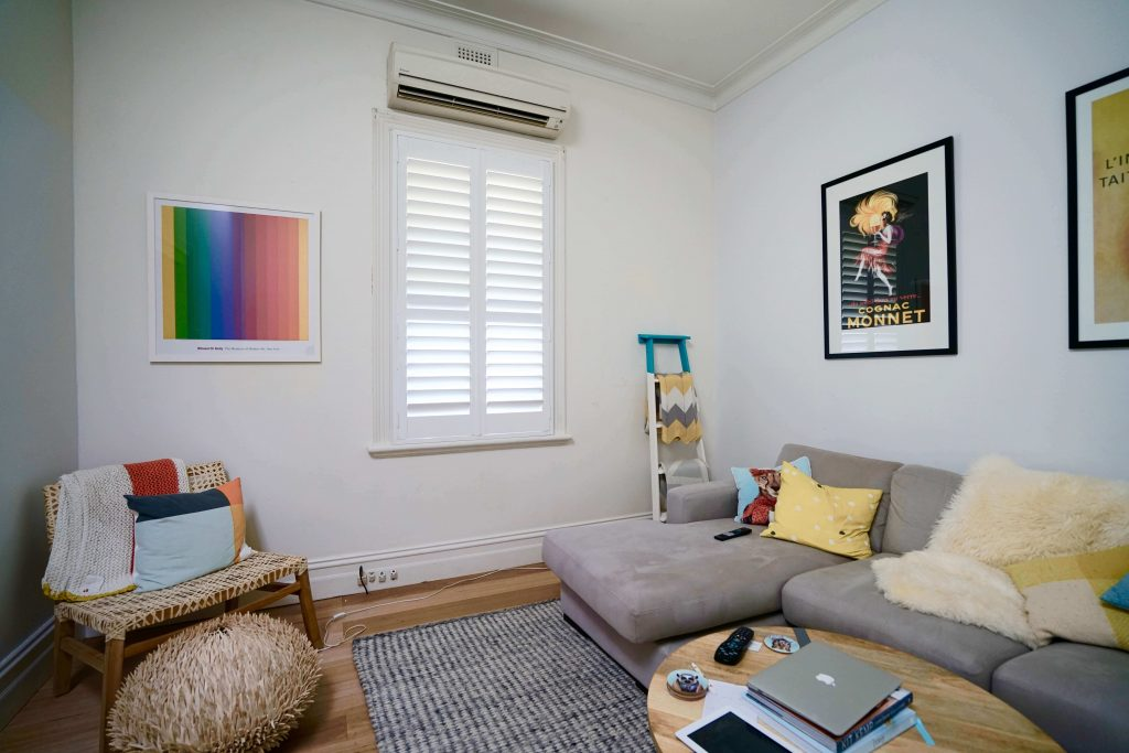 White plantation shutter covering a sash window located in the lounge room of a cottage house in Melbourne.