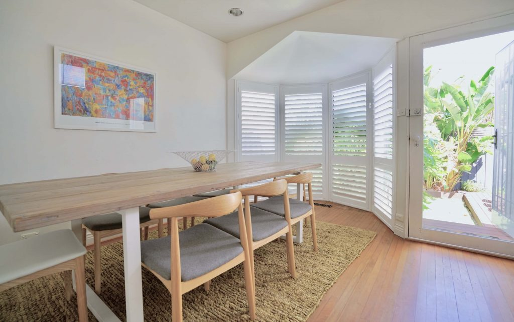 White Plantation Shutters covering a large bay window located in a kitchen.