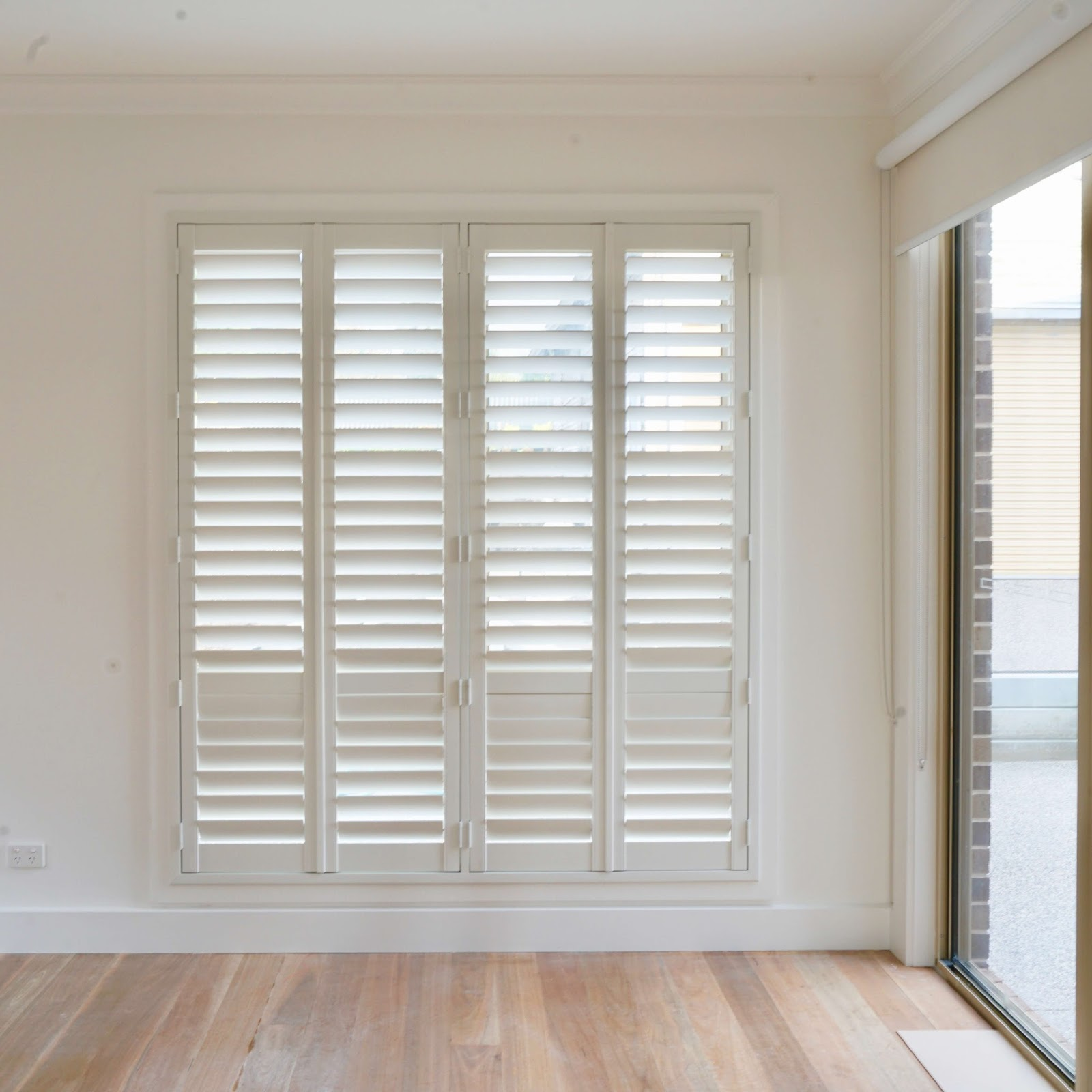 White Teak Plantation Shutters installed over a window next to a sliding door.