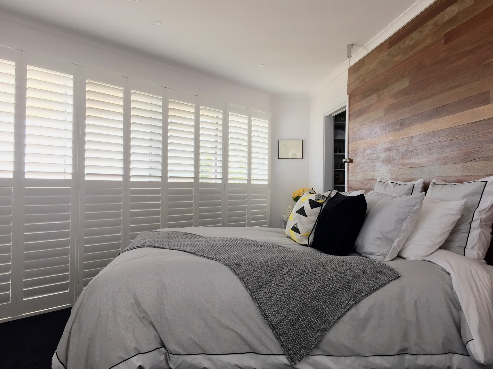 White Plantation Shutters made using basswood installed over a large bedroom sliding door.