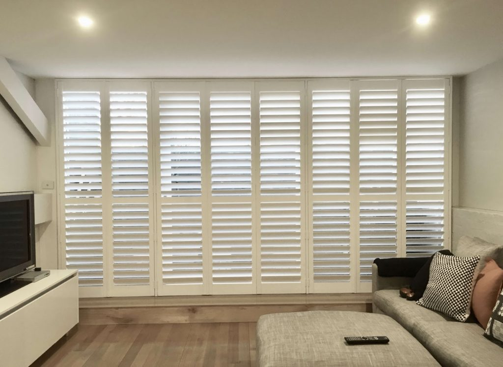 White plantation shutters made using white teak timber over a large window opening