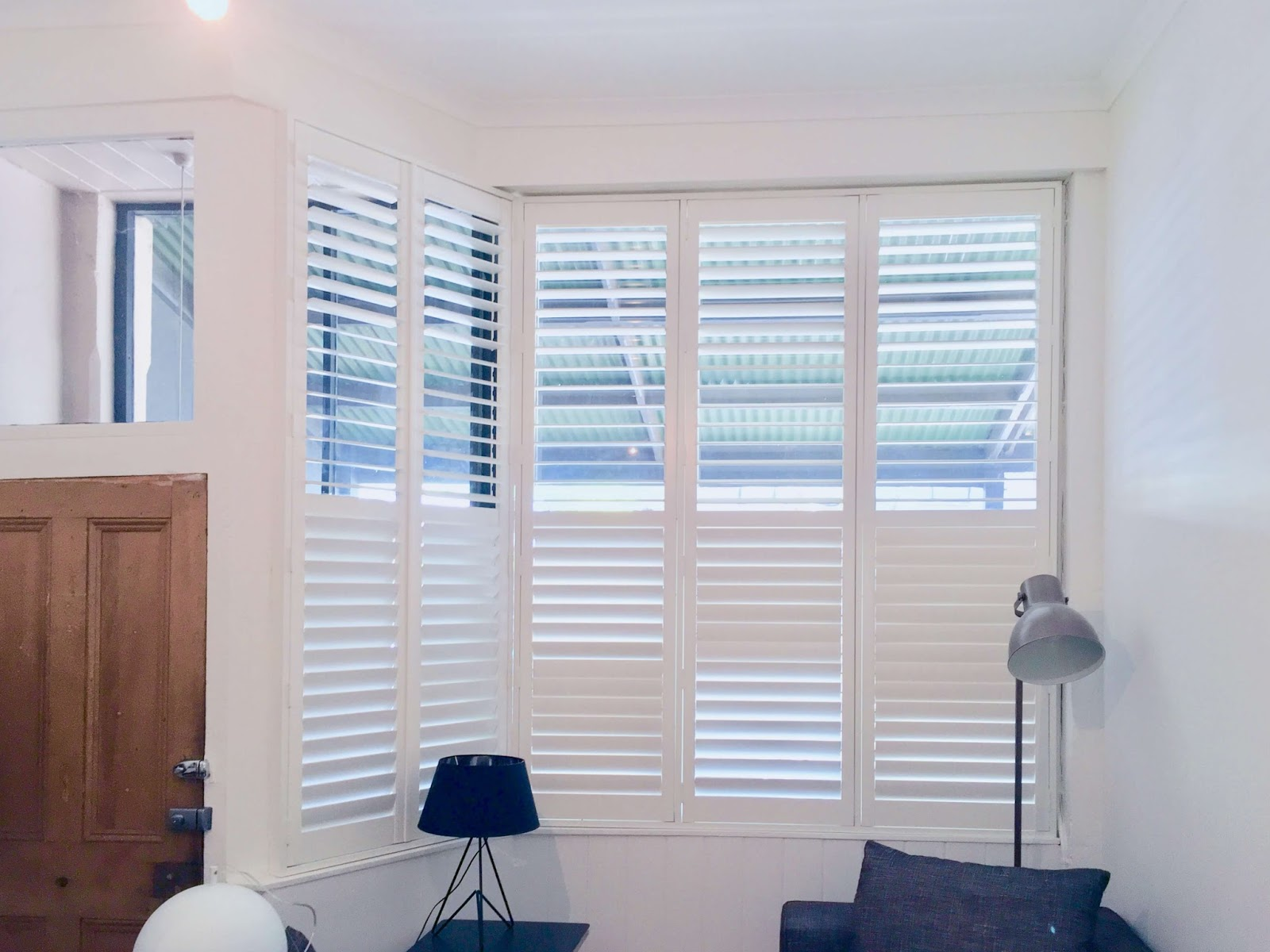 White plantation shutters fitted over a bay window.