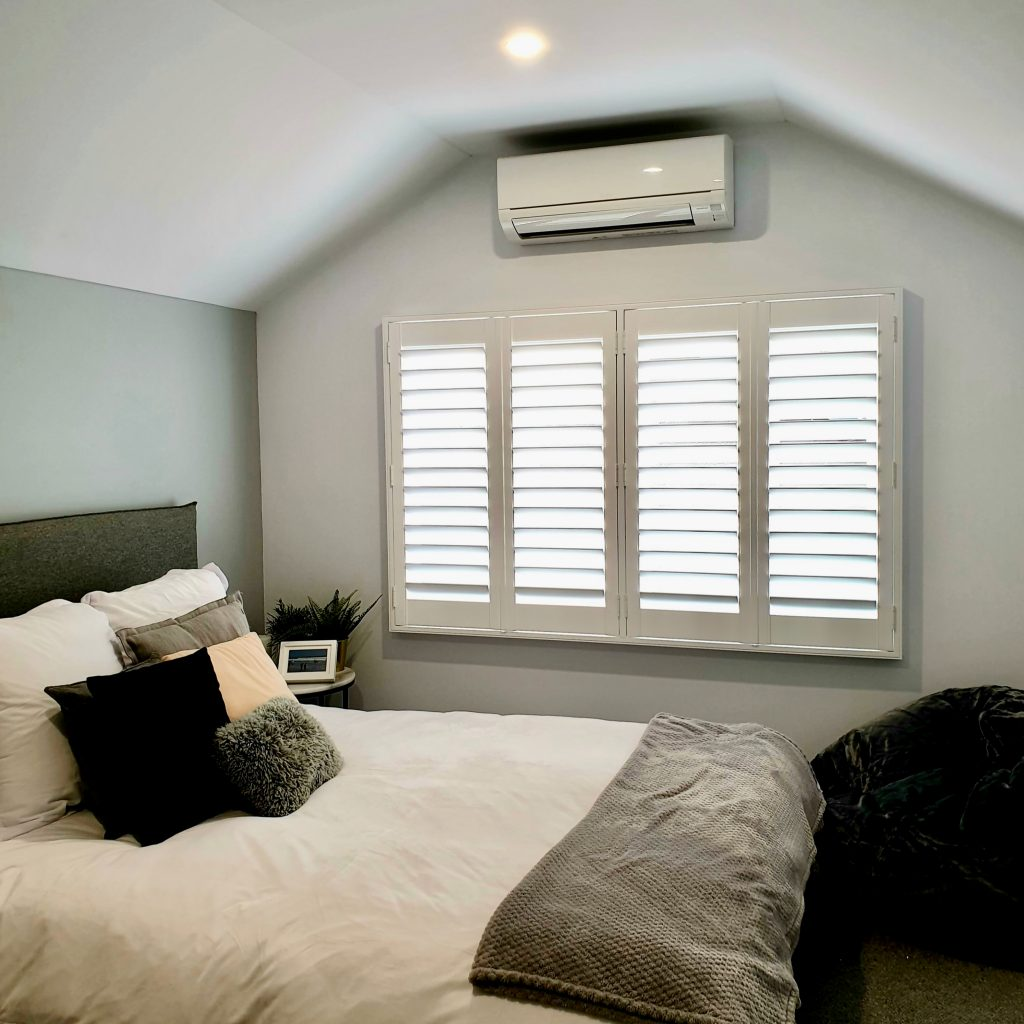 White plantation shutters with four panels in a bedroom with contenporary decor