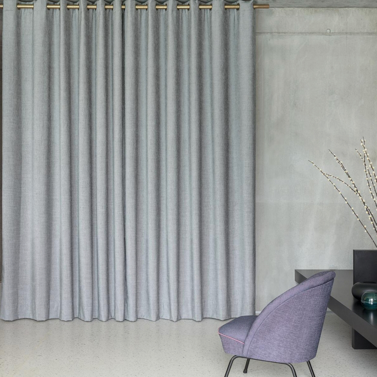 Grey Zepel Caption fabric curtains hanging on a gold rod in a room with concrete walls