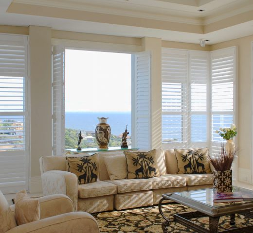 White plantation shutters covering large floor to ceiling windows with ocean views in a house located in Mt Martha.
