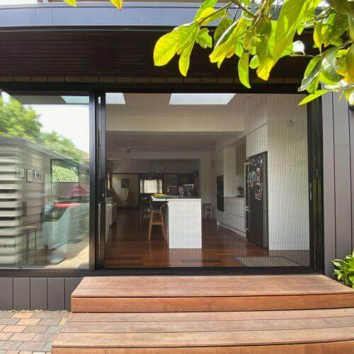 Black retractable fly screen installed over a sliding door in Port Melbourne.