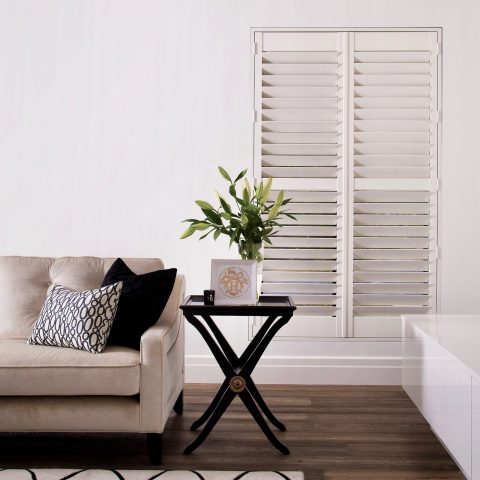 White plantation shutters made with basswood with 89 milimeter louvres in a lounge room
